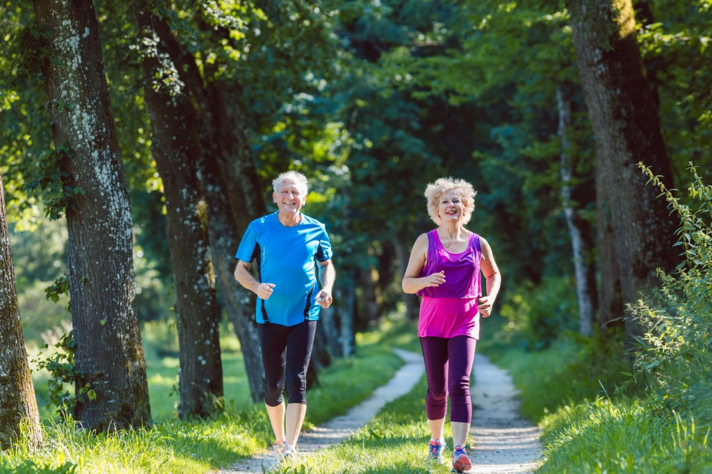 Full length front view of two active seniors with a healthy lifestyle smiling while jogging together outdoors in the park